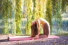 Портрет молодой женщины в парке города осени Девушка спорта делая йогу снаружи Стоковые Изображения RF