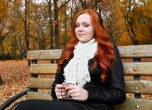 Портрет молодой женщины в парке осени, слушая к музыке на наушниках Стоковое Изображение RF