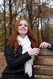 Портрет молодой женщины в парке осени, слушая к музыке на наушниках Стоковое Изображение