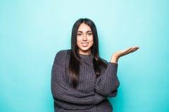 Портрет молодой женщины в свитере с открытой ладонью изолированной над голубой предпосылкой стоковые изображения rf