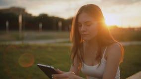 Портрет молодой женщины в eBook чтения парка, заходе солнца на backgound сток-видео