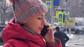 Портрет молодой женщины говоря по телефону пока идущ в снежный город зимы движение медленное сток-видео
