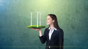 Портрет молодой женщины держа ветрянку на открытой ладони руки, над изолированной предпосылкой студии Дело, концепция eco Стоковое Фото