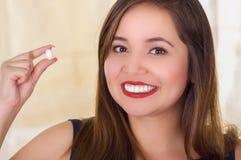 Портрет молодой женщины держа в ее руке таблетку мягкого желатина влагалищные или суппозиторие, обработку заболеваний  Стоковое Изображение RF