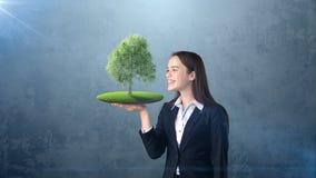 Портрет молодой женщины держа зеленое дерево на открытой ладони руки, над изолированной предпосылкой студии Дело, концепция eco Стоковые Изображения RF