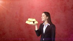 Портрет молодой женщины держа золотые бары на открытой ладони руки, над изолированной предпосылкой студии владение домашнего ключ Стоковые Фотографии RF
