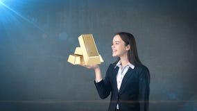 Портрет молодой женщины держа золотые бары на открытой ладони руки, над изолированной предпосылкой студии владение домашнего ключ Стоковые Изображения