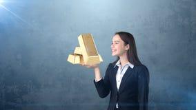 Портрет молодой женщины держа золотые бары на открытой ладони руки, над изолированной предпосылкой студии владение домашнего ключ Стоковое Фото