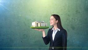 Портрет молодой женщины держа современный дом на открытой ладони руки, над изолированной предпосылкой студии владение домашнего к Стоковые Фото