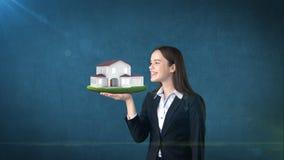 Портрет молодой женщины держа современный дом на открытой ладони руки, над изолированной предпосылкой студии владение домашнего к Стоковые Изображения RF