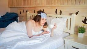 Портрет молодой женщины имея кофе в кровати на утре Стоковые Фото