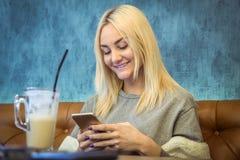 Портрет молодой женщины используя умный телефон в кофейне стоковое фото rf