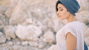 Портрет молодой женщины на предпосылке утесов и камней Гордость, самоуважение, заносчивость видеоматериал