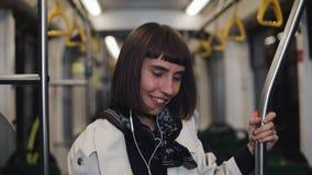 Портрет молодой женщины нося в пальто с наушниками слушая музыку и смешной переход танцев публично ?? видеоматериал