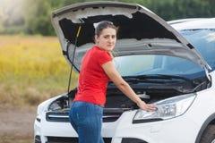 Портрет молодой женщины осадки стоя на сломленном автомобиле и смотря в камере Стоковое Изображение
