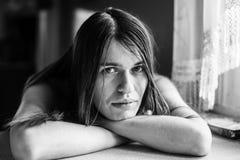 Портрет молодой женщины при длинные волосы сидя на таблице Стоковая Фотография RF