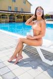 Портрет молодой женщины при стекло коктеиля охлаждая в тропическом солнце около бассейна на шезлонге красивейшие детеныши женщины Стоковые Фото