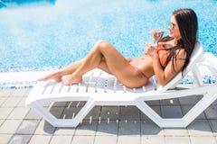 Портрет молодой женщины при стекло коктеиля охлаждая в тропическом солнце около бассейна на шезлонге красивейшие детеныши женщины Стоковое Фото