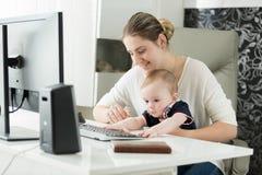 Портрет молодой женщины работая на офисе компьютера дома и смотря после ее сына младенца Стоковое Изображение