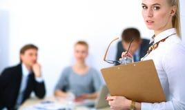 Портрет молодой женщины работая на офисе стоя с папкой Стоковые Фотографии RF