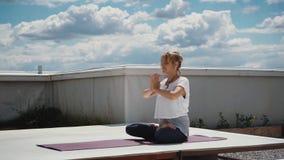 Портрет молодой женщины сидя в представлении лотоса и кладя руки в namaste сток-видео