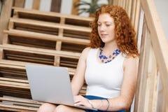 Портрет молодой женщины сидя на лестницах в офисе Стоковое Изображение RF