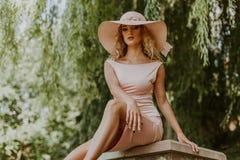 Портрет молодой женщины сидя на скамейке в парке Стоковая Фотография