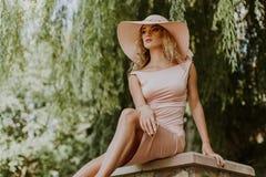 Портрет молодой женщины сидя на скамейке в парке Стоковые Изображения RF