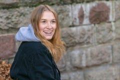 Портрет молодой женщины смеясь и смотря в направлении камеры стоковое изображение