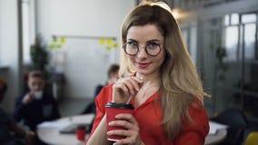 Портрет молодой женщины смотря камеру усмехаясь пока стекла привлекательной женщины стекел касаний нося в акции видеоматериалы