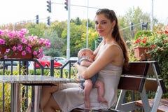 Портрет молодой женщины, счастливой новой матери ребенка пока она кормит грудью публично, нянча милого младенца сидя на стенде стоковое фото rf