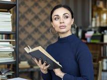 Портрет молодой женщины с книгой в библиотеке Стоковые Фото