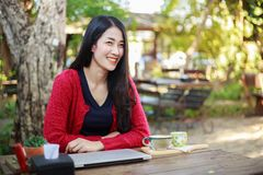 Портрет молодой женщины с компьтер-книжкой и кофе в саде Стоковое фото RF