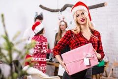 Портрет молодой женщины с розовым giftbox дома на переднем плане Красивая блондинка в шляпе Санты, красная рубашка в a Стоковое фото RF