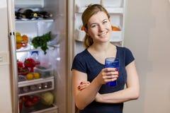 Портрет молодой женщины с стеклом воды перед холодильником вполне еды стоковые изображения
