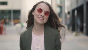 Портрет молодой женщины с телефоном усмехаясь и смотря камеру видеоматериал