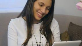Портрет молодой женщины усмехаясь, пока читающ сообщения от парня на планшете на софе стоковая фотография rf