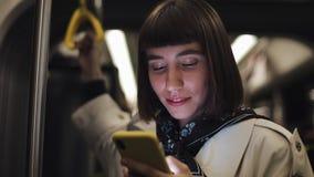Портрет молодой женщины хипстера держит поручень, используя смартфон стоя публично переход Света города акции видеоматериалы