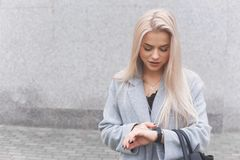 Портрет молодой женщины blondhair элегантно одетой в пальто использует умный браслет стоя outdoors стоковое изображение