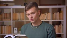 Портрет молодой книги чтения студента внимательно будучи заинтересованным и сконцентрированной на библиотеке видеоматериал