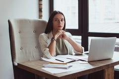 Портрет молодой коммерсантки сидя с ее компьтер-книжкой в офисе стоковые изображения rf