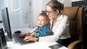 Портрет молодой коммерсантки смотря после ее сына малыша в офисе Стоковое Изображение RF