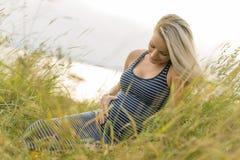 Портрет молодой красивой белокурой беременной женщины на стороне пляжа Стоковая Фотография