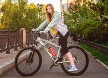 Портрет молодой красивой белокурой девушки с велосипедом Стоковые Изображения