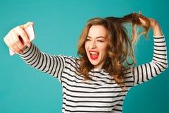 Портрет молодой красивой белокурой женщины smiley делая selfie и Стоковое Фото