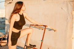 Портрет молодой красивой девушки в черных коротких шортах и черной верхней части представляя на крыше дома на заходе солнца стоковое изображение rf