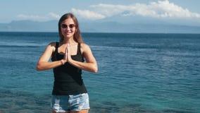 Портрет молодой красивой девушки делает тренировку йоги, океан на предпосылке, замедленном движении сток-видео