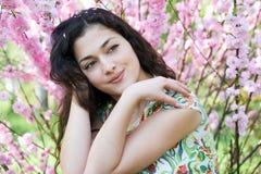 Портрет молодой красивой девушки на пинке цветет предпосылка, поднимающее вверх стороны близкое Стоковые Изображения