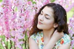 Портрет молодой красивой девушки на пинке цветет предпосылка, поднимающее вверх стороны близкое Стоковые Изображения RF