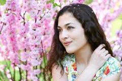 Портрет молодой красивой девушки на пинке цветет предпосылка, поднимающее вверх стороны близкое Стоковое Фото